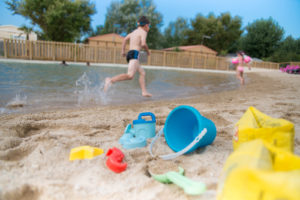 New lagoon with its sandy beach and massage jets in camping le Petit Paris